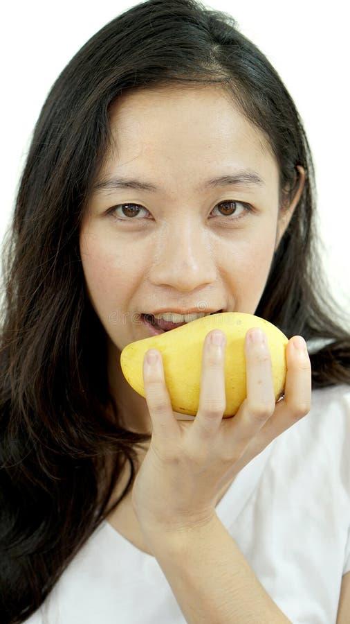 吃芒果的亚裔美丽的妇女 夏天欢欣热带frui 库存图片