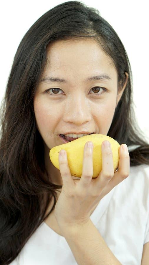 吃芒果的亚裔美丽的妇女 夏天欢欣热带frui 免版税库存图片