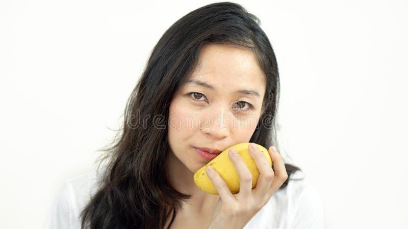 吃芒果的亚裔美丽的妇女 夏天欢欣热带frui 图库摄影