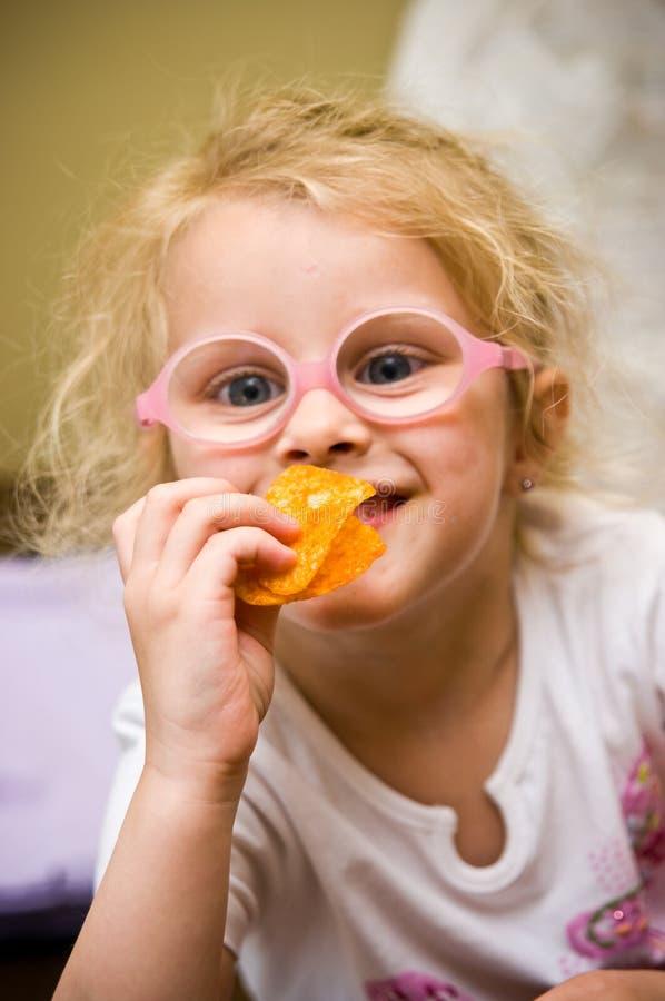 吃芯片的女孩做滑稽的面孔 免版税库存照片