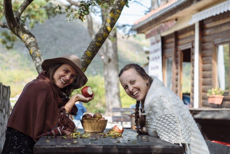 吃苹果和微笑的两个Contryside朋友 免版税图库摄影