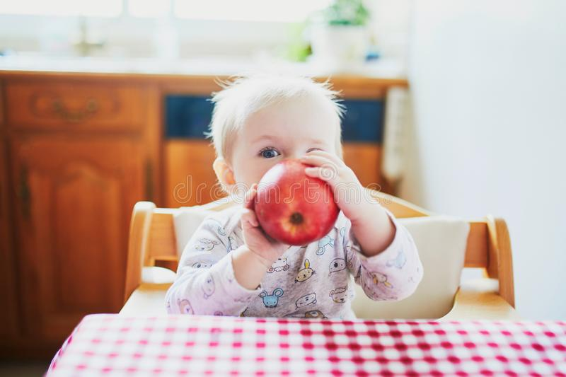 吃苹果的可爱宝贝女孩在厨房里 库存照片