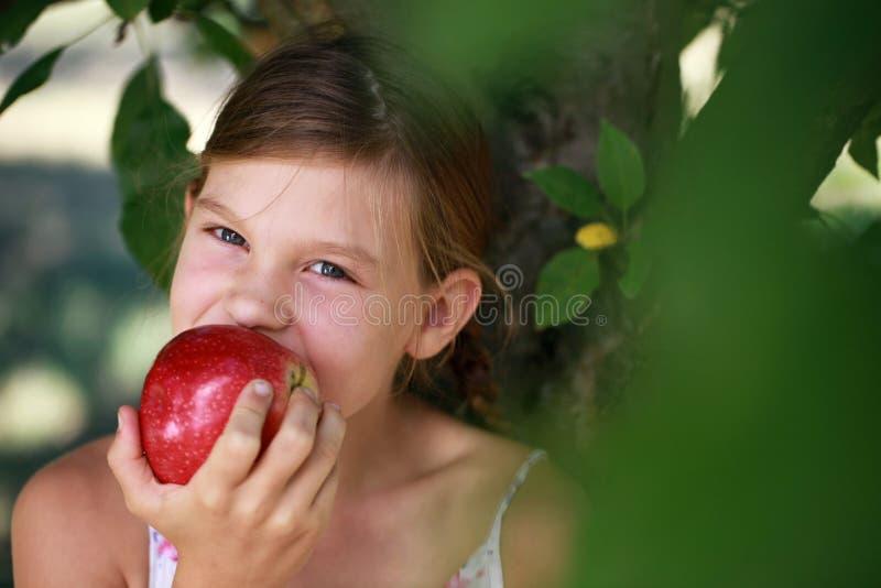 吃苹果的女孩 免版税图库摄影