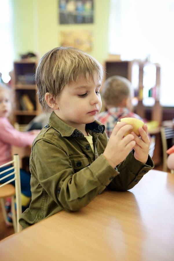 吃苹果的孩子在幼儿园 库存照片
