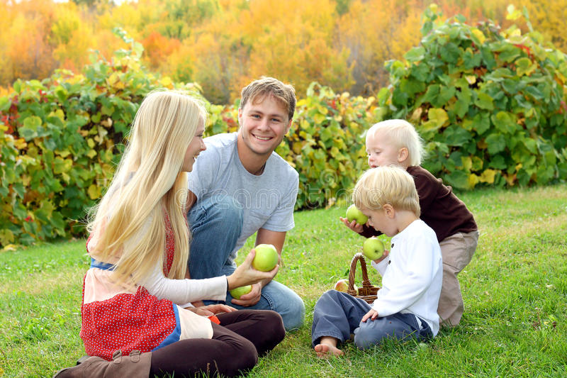 吃苹果的家庭在果树园在秋天 库存照片