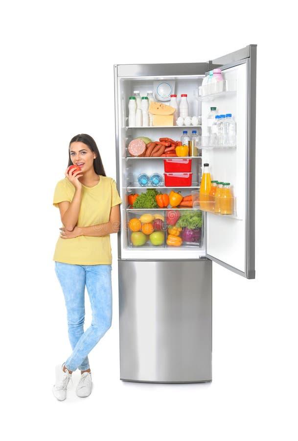 吃苹果的年轻女人在开放冰箱附近 免版税库存照片