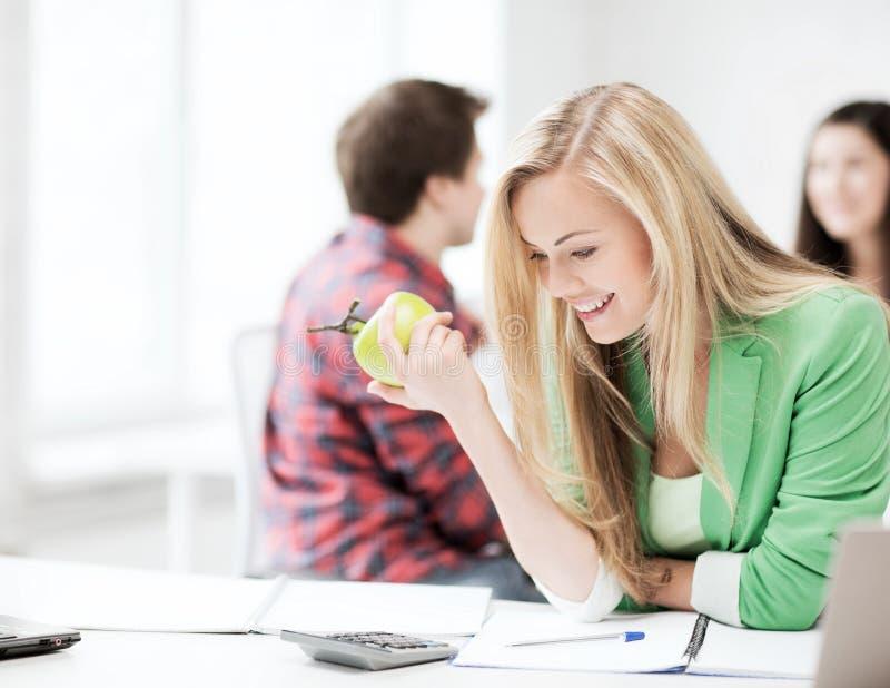 吃苹果的微笑的学生女孩在学校 图库摄影