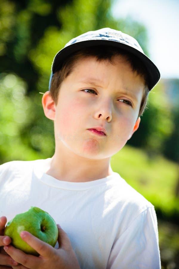 吃苹果的男孩 免版税库存照片