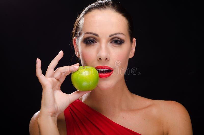 吃苹果的美丽,时髦的妇女 免版税图库摄影