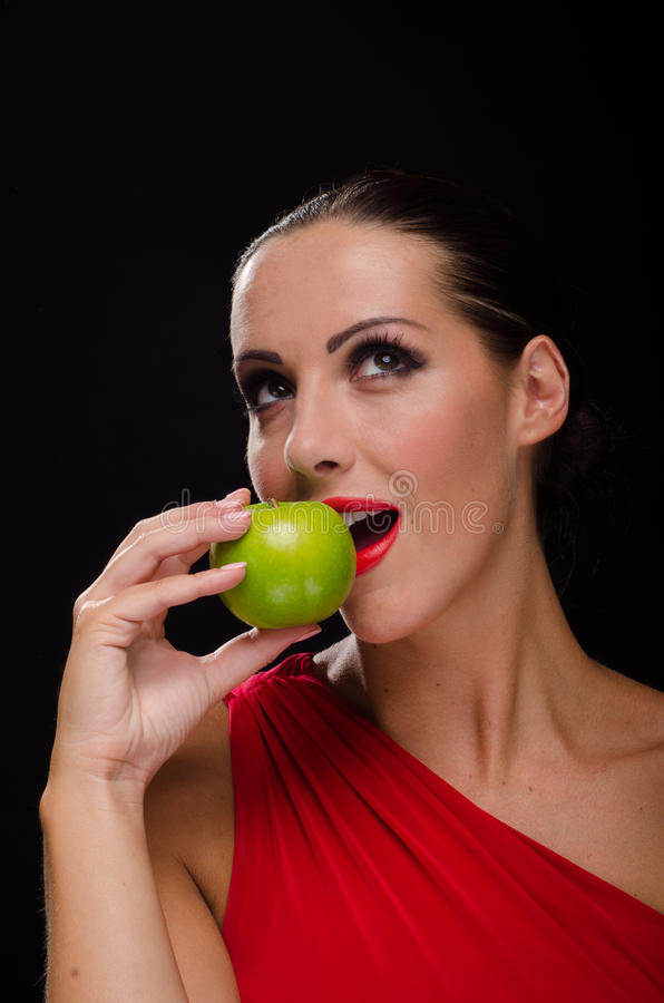 吃苹果的美丽,时髦的妇女 免版税库存图片