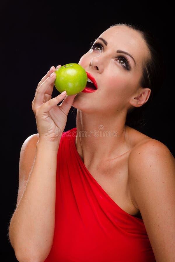 吃苹果的美丽,时髦的妇女 库存图片