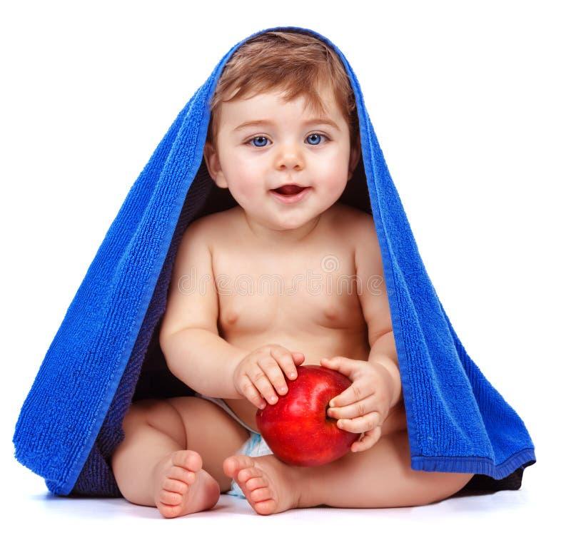吃苹果的逗人喜爱的男婴 图库摄影