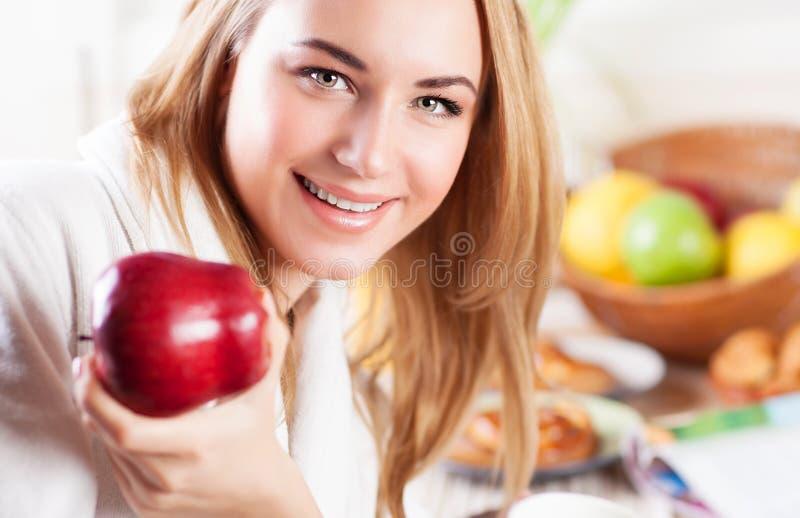 吃苹果计算机的愉快的妇女 图库摄影
