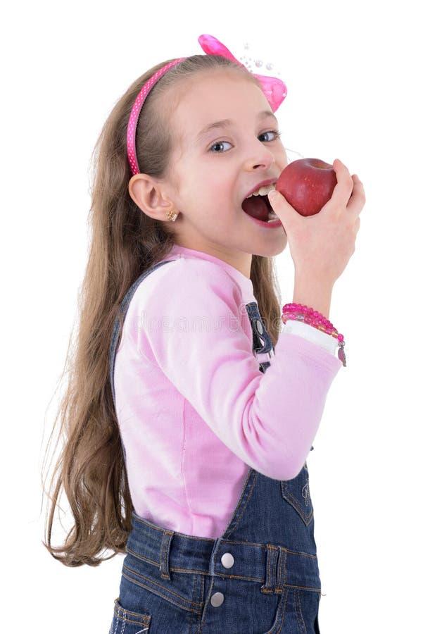 吃苹果计算机的年轻白肤金发的女孩 库存图片
