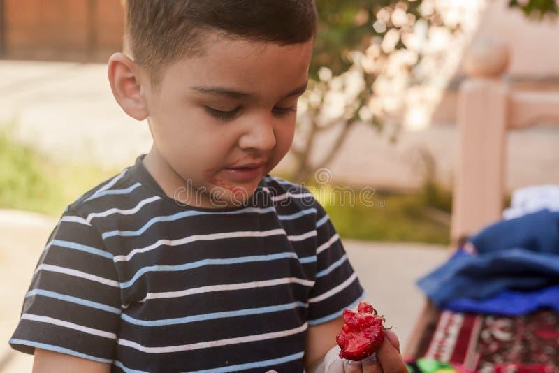 吃草莓的一个小男孩 E 一个小孩吃一个美味的草莓 免版税库存照片