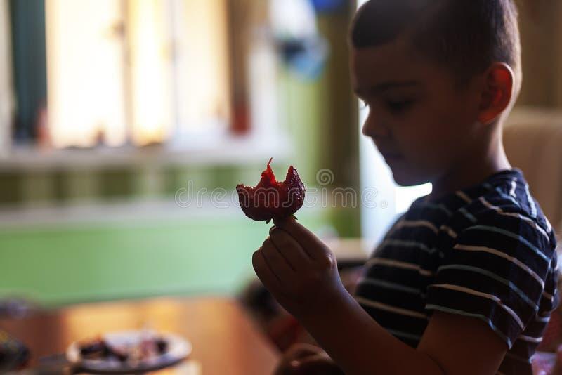 吃草莓的一个小男孩 E 库存图片