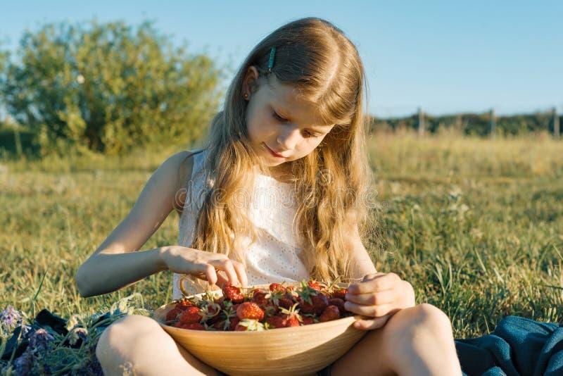 吃草莓的可爱的儿童女孩 自然背景,绿色草甸,乡村模式 免版税库存照片
