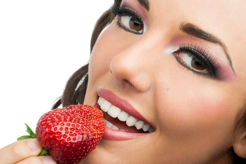 吃草莓的可爱的女孩。 免版税库存照片