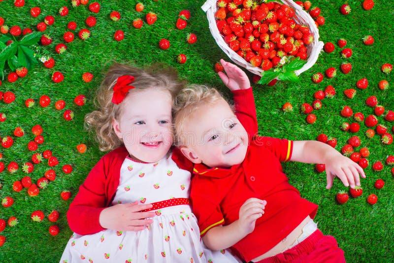 吃草莓的孩子 免版税库存照片