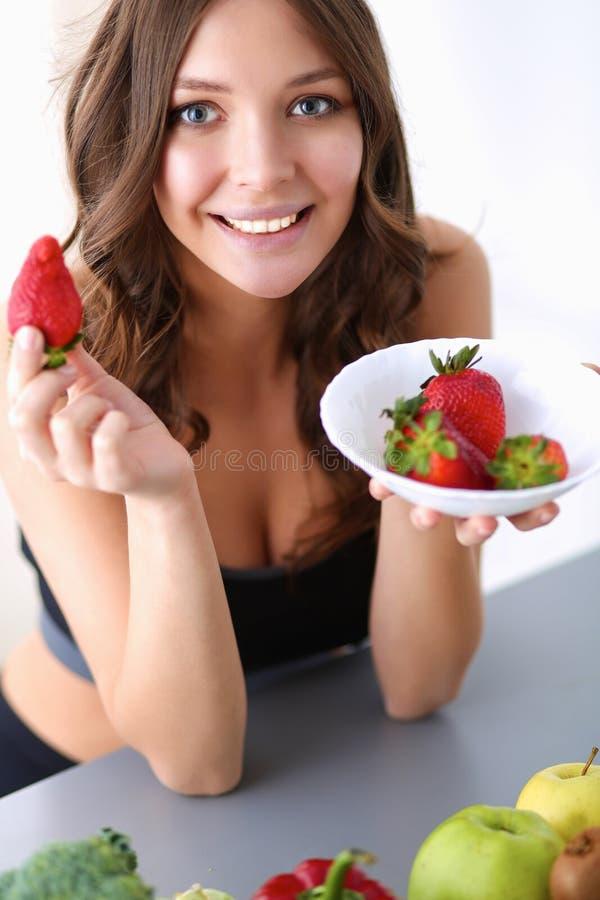 吃草莓的微笑的妇女 关闭女性面孔画象 免版税库存图片