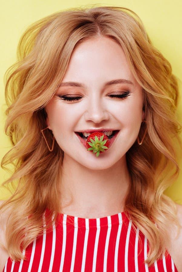 吃草莓的性感的妇女 肉欲的嘴唇 库存照片