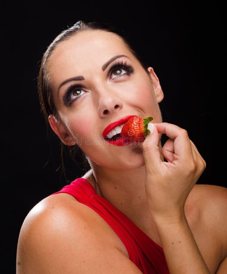 吃草莓的美丽,时髦的妇女 免版税库存照片