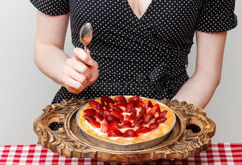 吃草莓馅饼的妇女 免版税图库摄影