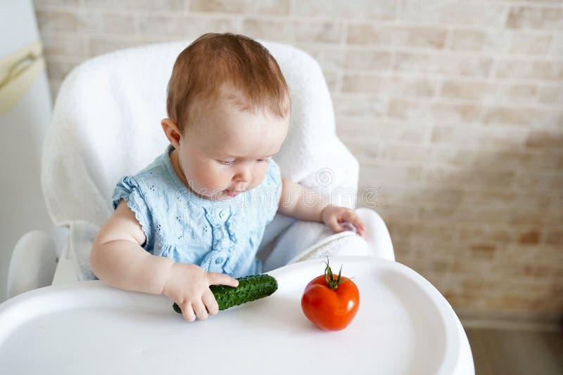 吃菜的婴孩 绿色黄瓜在女孩手上在晴朗的厨房里 r 快餐或早餐为 免版税库存图片