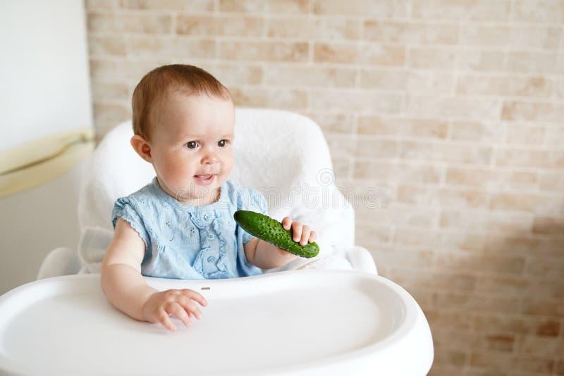 吃菜的婴孩 绿色黄瓜在女孩手上在晴朗的厨房里 r 快餐或早餐为 免版税图库摄影