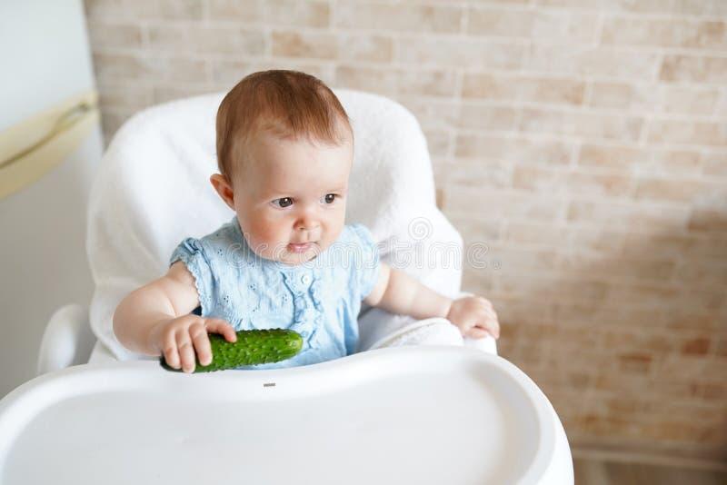 吃菜的婴孩 绿色黄瓜在女孩手上在晴朗的厨房里 r : 库存照片