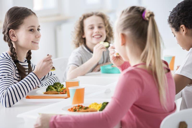 吃菜的微笑的女孩在午休期间 图库摄影