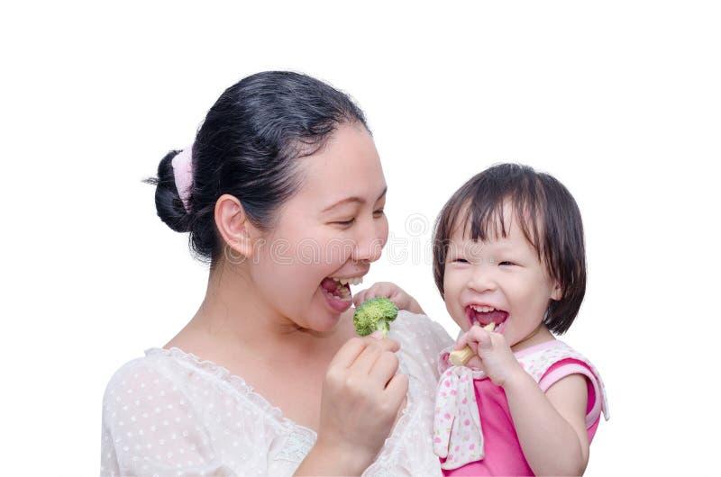 吃菜的母亲和她的女儿 免版税库存照片