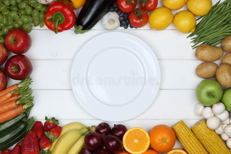 吃蔬菜和水果在空的板材的健康素食主义者 库存照片