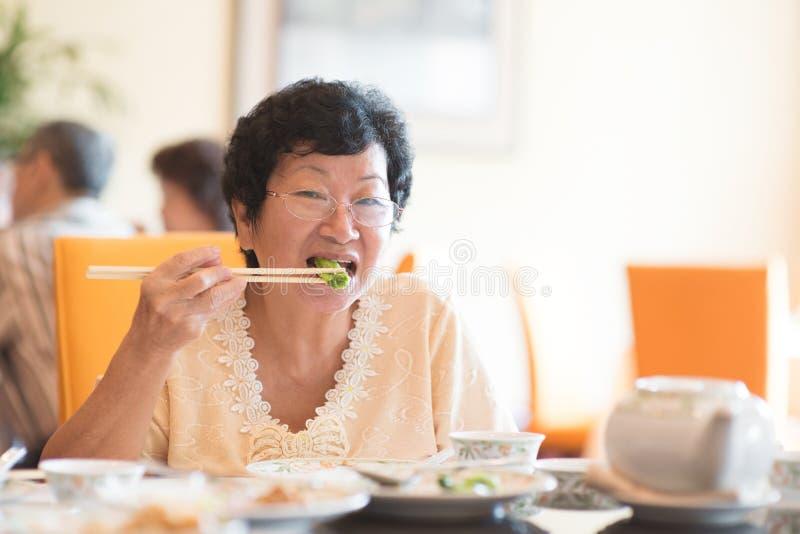 吃蔬菜的高级亚裔妇女 免版税库存图片