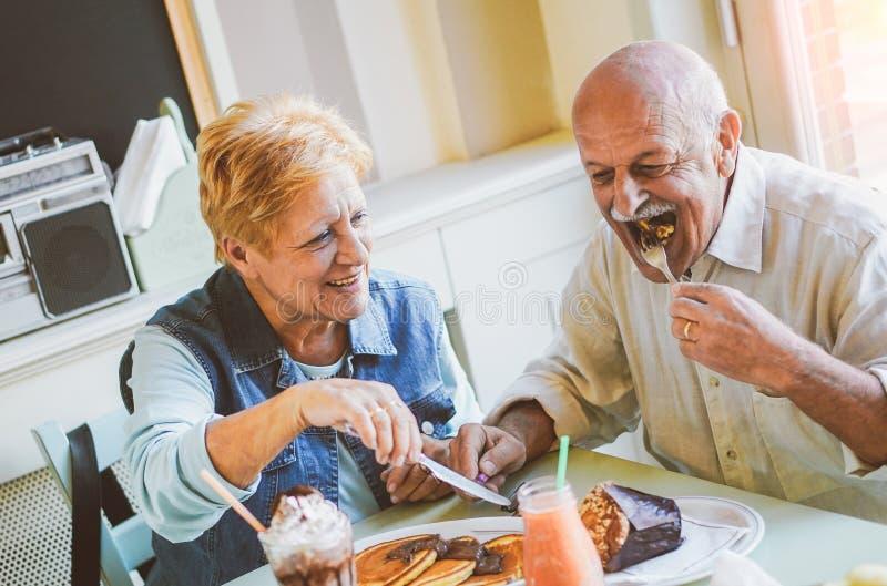 吃薄煎饼在酒吧餐馆-成熟人民的愉快的前辈夫妇获得在家一起用餐的乐趣 免版税库存照片
