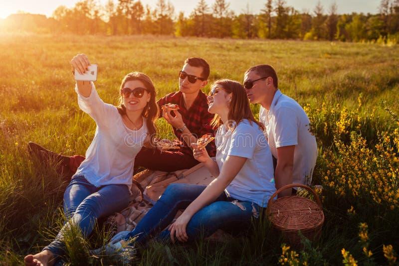 吃薄饼外部和采取selfie的朋友 妇女和人有野餐在日落 快餐概念 库存图片