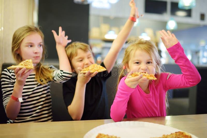 吃薄饼的三逗人喜爱的滑稽的兄弟姐妹在室内餐馆或咖啡馆 免版税库存图片