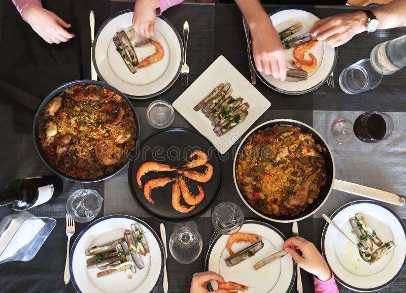 吃西班牙塔帕纤维布的家庭顶视图在从高视角的一张白色桌附近 库存照片