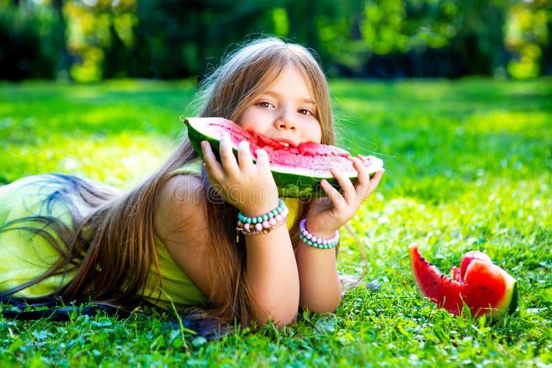 吃西瓜的女孩室外 免版税库存图片