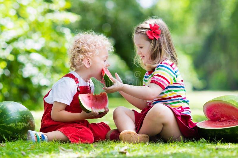 吃西瓜的孩子在庭院里 免版税库存照片
