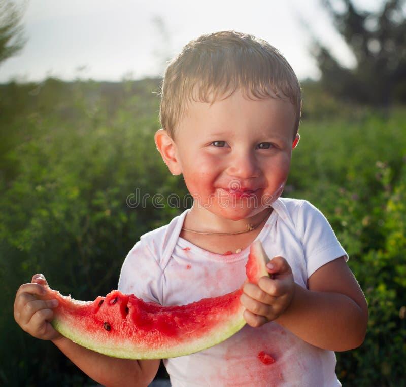 吃西瓜的小婴孩户外 免版税图库摄影