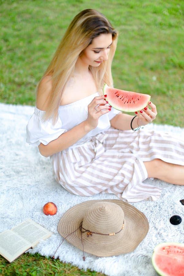 吃西瓜的年轻白种人女孩,坐格子花呢披肩在果子和帽子附近有草的在背景中 库存照片