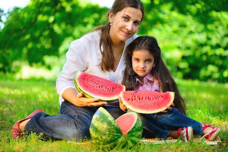 吃西瓜的愉快的印地安家庭 图库摄影