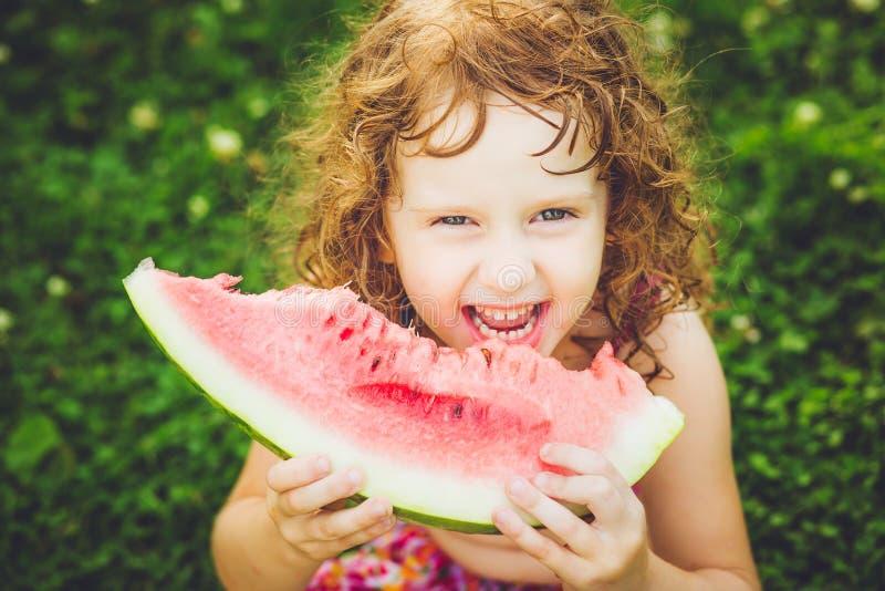 吃西瓜的愉快的小女孩在夏天公园 Instagram fi 免版税库存照片