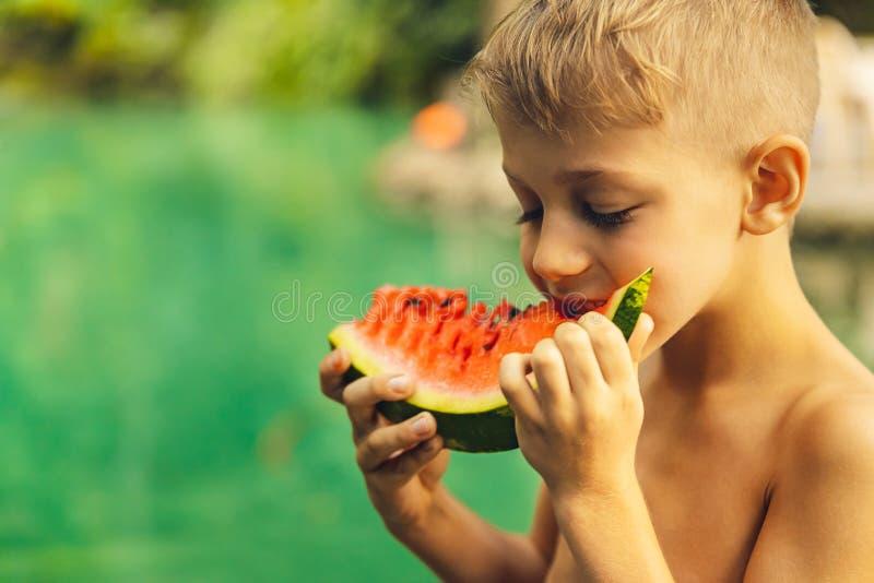 吃西瓜的愉快的男孩 库存图片