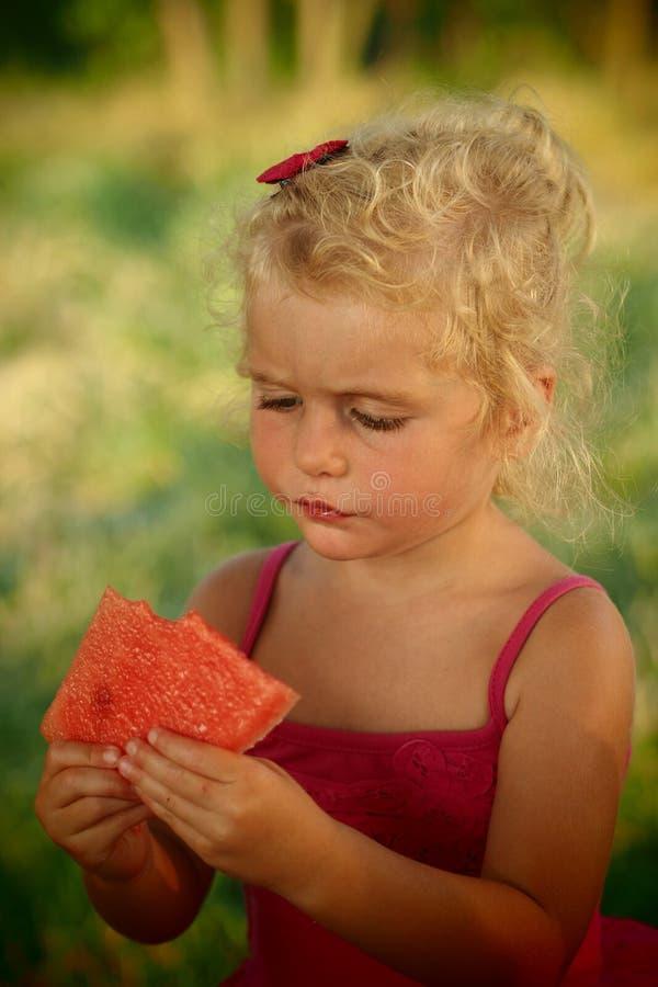 吃西瓜的白肤金发的女婴 免版税图库摄影