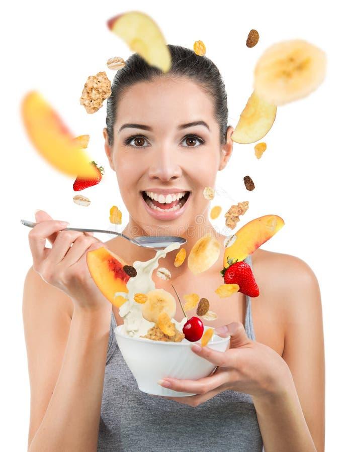 吃谷物和果子的美丽的少妇 免版税库存照片