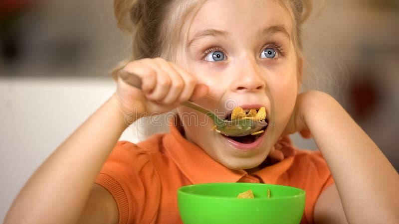 吃谷物特写镜头,开胃早餐,早晨玉米片膳食的逗人喜爱的女孩 免版税库存照片