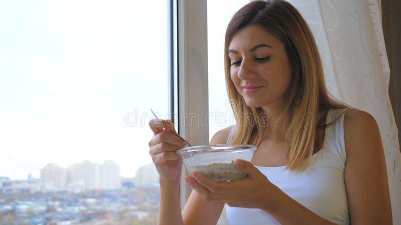 吃谷物用牛奶的妇女在看的碗外面站立在窗口和外面 库存照片