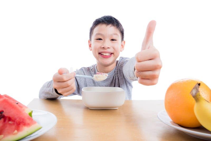 吃谷物用酸奶的年轻男孩早餐 免版税图库摄影
